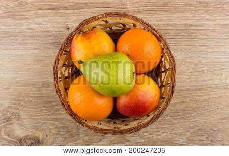 Tangerines, Pears And Nectarines In Wicker Basket On Wooden Table