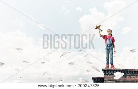 Cute happy kid girl on building top playing with retro plane model