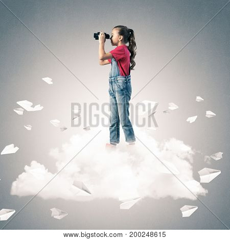 Cute kid girl standing on cloud looking in binoculars and paper planes flying around