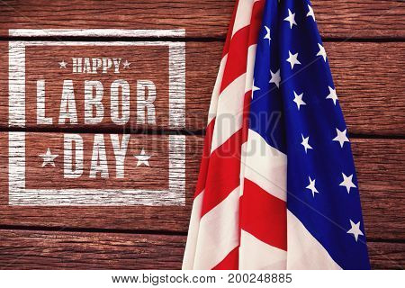 Composite image of happy labor day poster against american flag on a wooden table