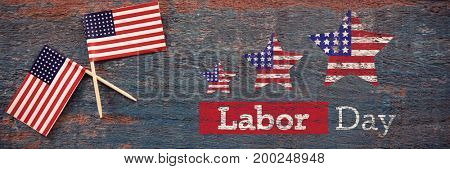 Composite image of labor day text with star shapes American flag against two american flags on a wooden table