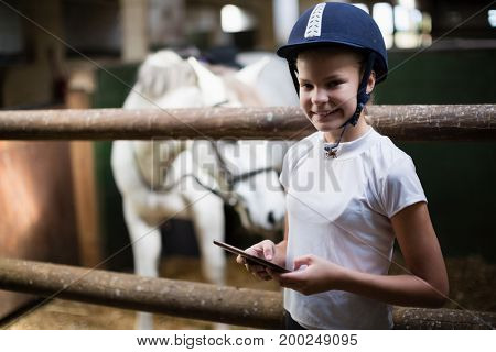 Portrait of teenage girl using digital tablet in the stable
