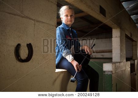 Portrait of girl sitting in stable