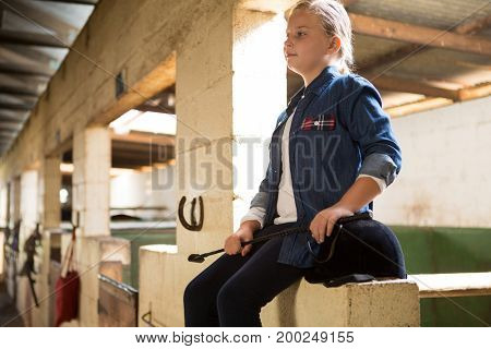 Thoughtful girl sitting in stable