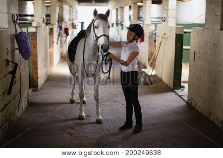 Teenage girl standing with horse in the stable