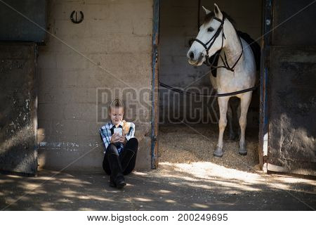 Happy teenage girl using mobile phone in the stable
