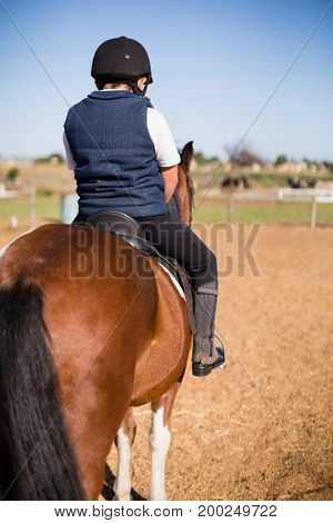 Rear-view of boy riding a horse in the ranch