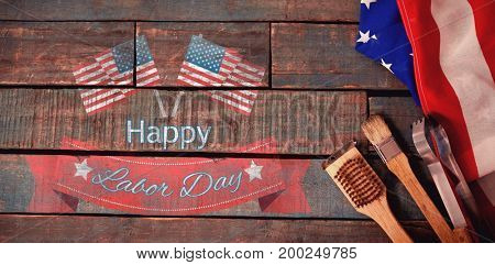 Happy labor day text badge with flags against basting brush and tong with american flag on table