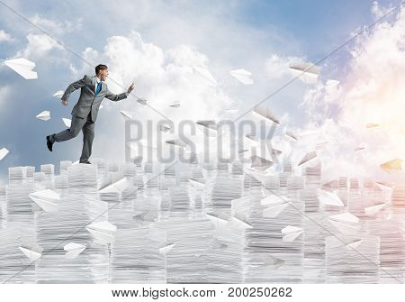 Businessman in black suit running with phone in hand among flying paper planes with cloudly skyscape on background. Mixed media.