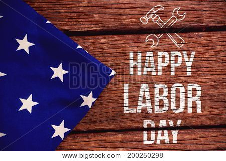 Digital composite image of happy labor day text with tools against american flag on a wooden table