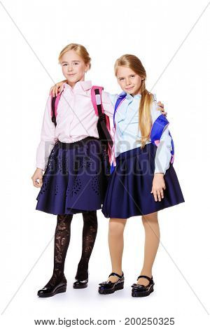 Two cute happy girls in school uniform posing at studio. School fashion. Isolated over white background. Full length portrait. Copy space.
