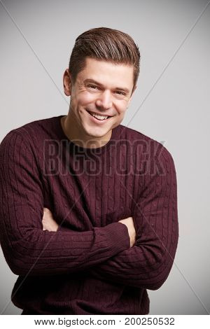 Smiling young white man with arms crossed looking to camera