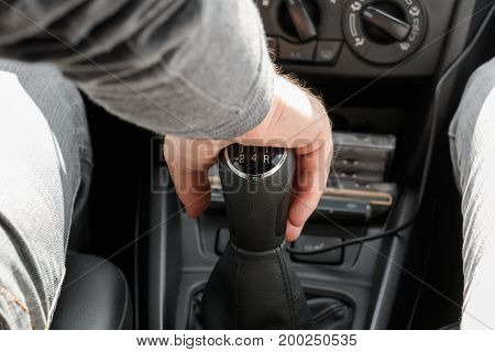 Male hand changes gear using the gearshift stick
