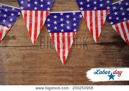 Digital composite image of happy labor day text with star shape against american flag buntings on table