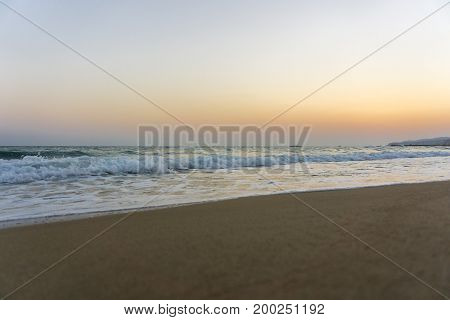 View on a Beach in the Morning Light of a beautiful beginning Sunrise. Close-up of long deserted Beach. Beach Background.