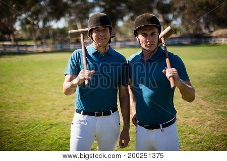 Portrait of two male jockeys standing in the ranch