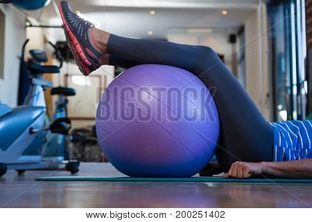 Mid-section of senior woman resting her legs on exercise ball at clinic