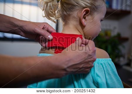 Physiotherapist sticking tape on girl patient in hospital