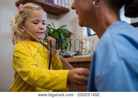 Cute little girl using stethoscope in hospital