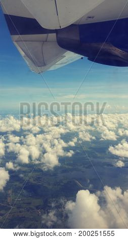 View of clouds and landscape from the window of an airplane