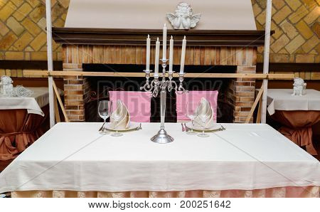 Table Setting Served For Two People With White Plates, Beige Table Napkins, Candlestick And Cutlery