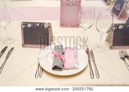 Rolled Table Napkin With Pink Ribbon And Bar Of Chocolate With Blank Space For Text On White Plate.