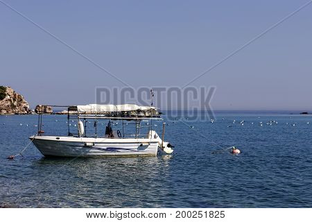 An old fishing boat on the background of the sea is moored offshore