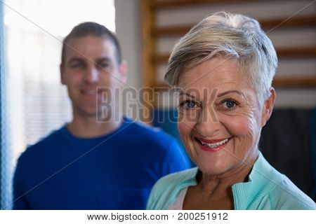Portrait of smiling senior woman standing in hospital