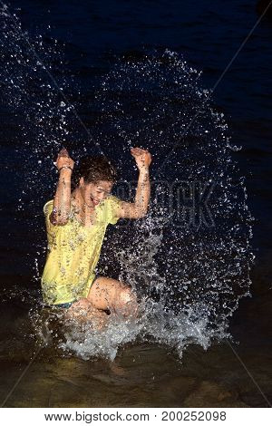 Happy pretty Asian woman open arms having fun in the sea playing with water splashes on tropical vacation at night.