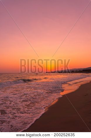 View on a deserted Beach in the warm Light of a beautiful Sunset. Close-up of long Beach at Sunset. Beach Background.