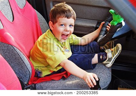 The boy with passion sits at the wheel of the car