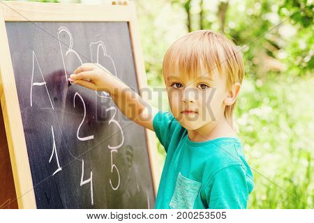 Cute Little Boy At Blackboard Practicing Counting And Math Outdoor.