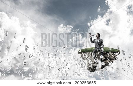 Young businessman sitting on island and screaming emotionally in megaphone