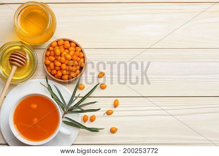 Sea buckthorn in wooden bowl, honey, Sea buckthorn juice on wooden table. top view with copy space