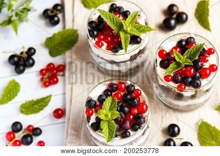 A sweet dessert of sponge cake with cream in a glass with fresh berries on wooden background.