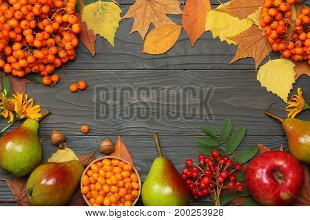 autumn background with colored leaves, apple, pear and rowan on wooden board. top view with copy space
