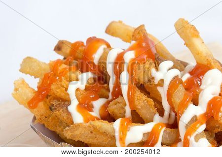 Hot and spicy french fries on a white plate with mayonnaise and tomato chili sauce