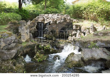 Little Waterfall In Summer Park With Rocks And Green Vegetable