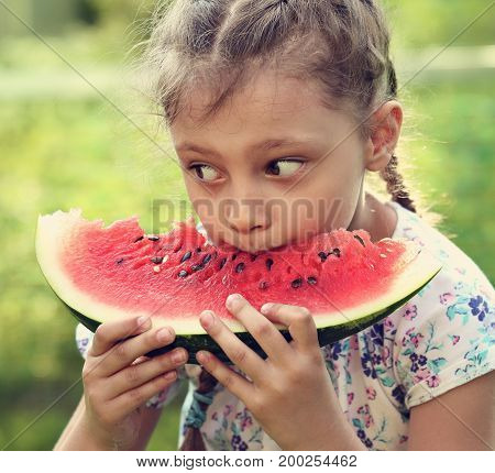 Beautiful Kid Girl Eating Big Red Watermelon With Fun Look On Summer Day Green Glass Background. Clo