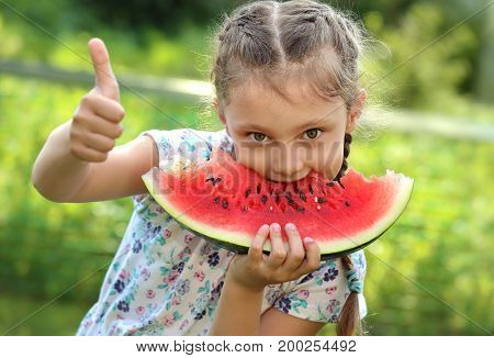Beautiful Kid Girl Eating Big Red Watermelon With Fun Humor Look And Showing Thumb Up On Summer Day