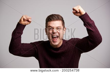 Portrait of a celebrating young white man with arms up