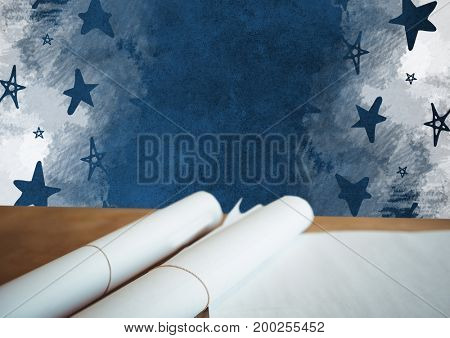Digital composite of Scrolls of paper plans on desk with blackboard and stars