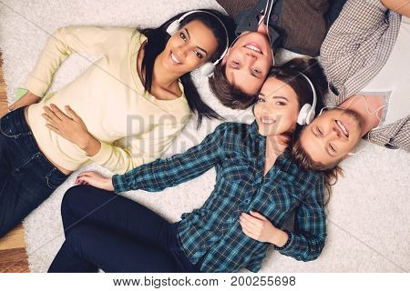 Happy multiracial friends listening music