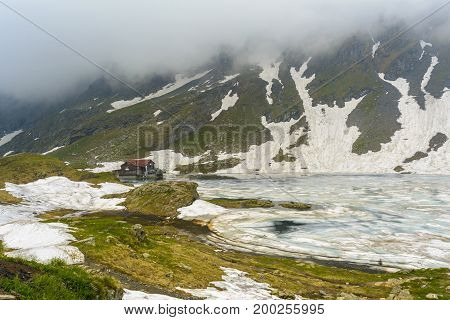 BALEA LAKE - JUNE 4 2015: Chalet on glacial lake Balea in Fagaras Mountains near the famous Transfagarasan road Sibiu county Romania. Is a glacier lake situated at 2034 m of altitude in the Fagaras Mountains from Carpathians chain.