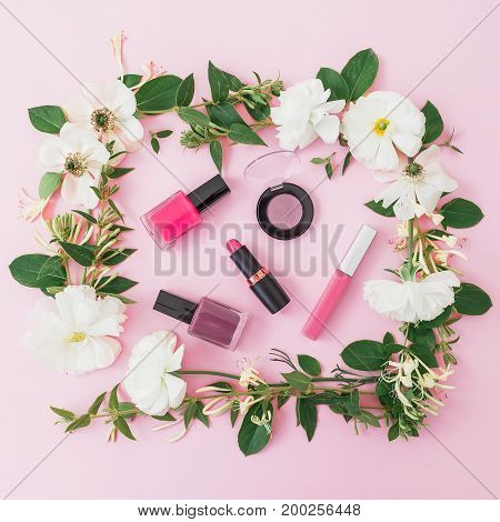 Beauty woman accessories of cosmetics, lipstick, eye shadows, nail polish and floral frame made of white flowers on pink background. Flat lay, top view.