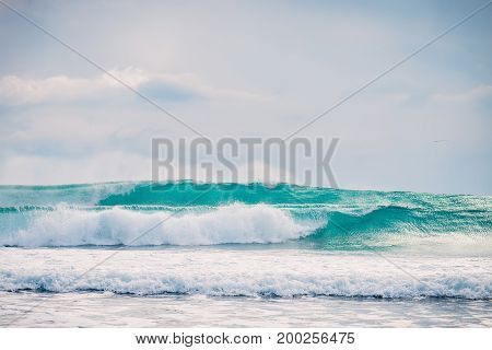 Blue ideal waves in tropical ocean. Clear turquoise waves in tropics