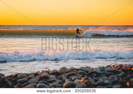 Surfer rides on the perfect ocean wave at sunset. Winter surfing