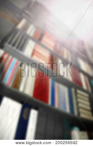 Blurred background: the big book shelfs in library with beams of bright light from the corner
