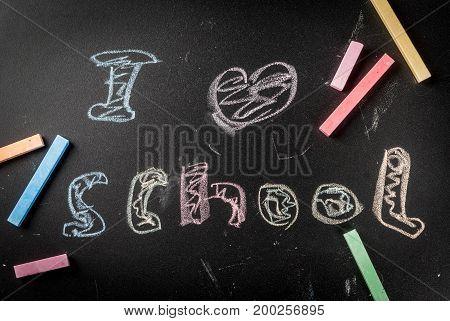 Back to school. September. Slate blackboard with chalk for drawing notebooks. Inscription I love school. Copy space