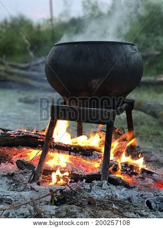 Twilight In The Tourist Camp. A Diluted Fire. A Pot Of Cooked Food Standing On The Fire. Tent Camp O
